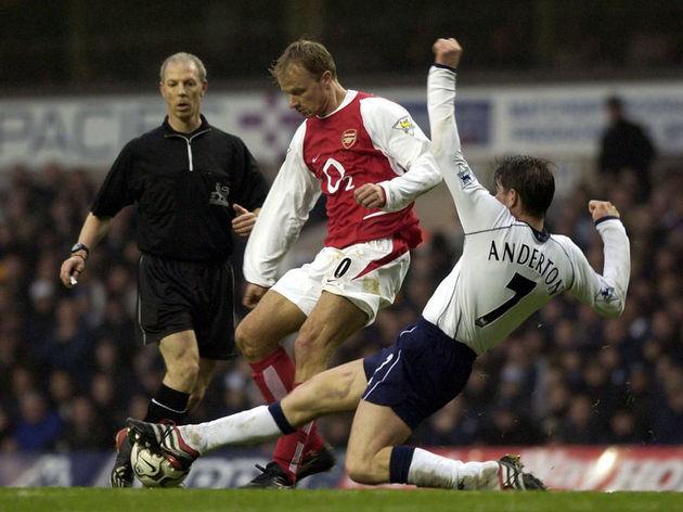 Dennis Bergkamp of Arsenal is tackled by Darren Anderton of Tottenham Hotspur