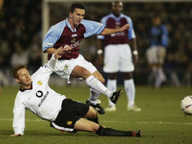 Paul Weller of Burnley hurdles a sliding tackle from Michael Stewart of Manchester United