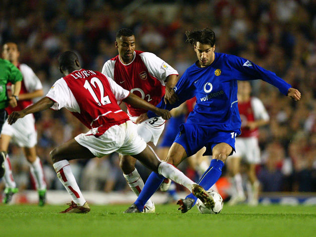 Ruud Van Nistelrooy of Manchester United is tackled by Lauren of Arsenal