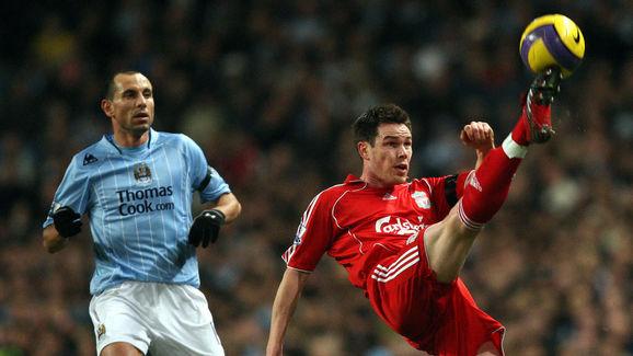 Steve Finnan (R) of Liverpool clears the